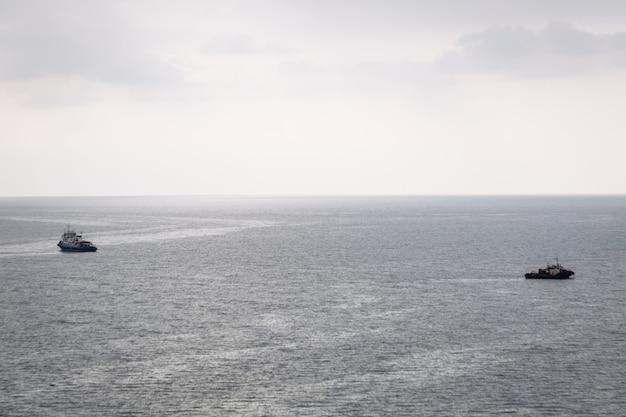 Dois barcos navegam em direções diferentes no mar em um dia nublado