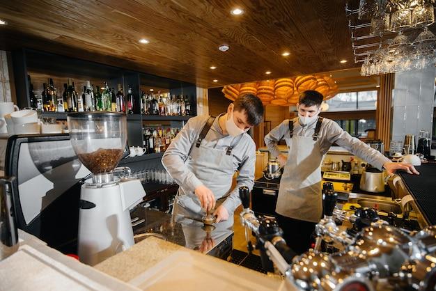 Dois baristas mascarados preparam um delicioso café no café-bar