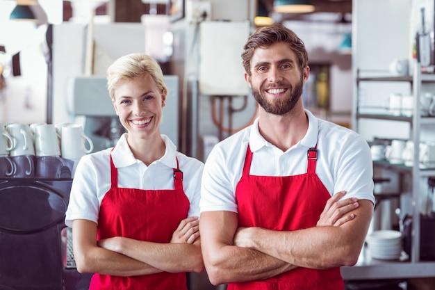 Dois baristas sorrindo para a câmera