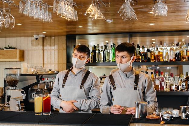 Dois bartenders elegantes com máscaras e uniformes durante a pandemia, preparando coquetéis