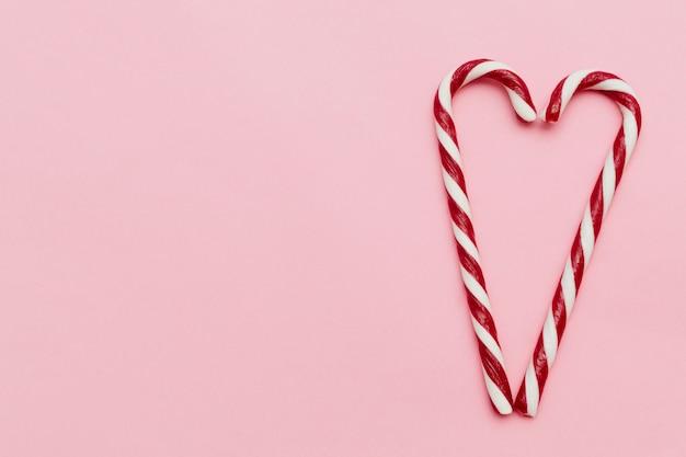 Dois bastões de doces formando um coração, no fundo rosa com espaço de cópia do conceito de dia dos namorados.