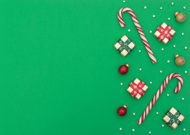 Dois bastões de natal com caixas de presente, bolas de natal vermelhas e douradas e miçangas sobre fundo verde. estilo liso leigo com espaço de cópia.