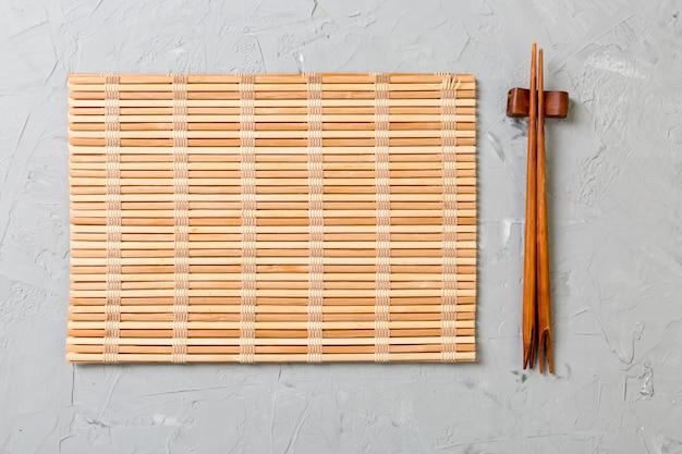Dois bastões de treino de sushi com tapete de bambu vazio