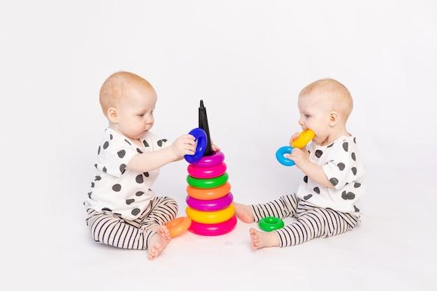 Dois bebês gêmeos de 8 meses brincam em um fundo branco isolado, desenvolvimento precoce de crianças até um ano de idade, uma criança pega um brinquedo de outro, um lugar para texto
