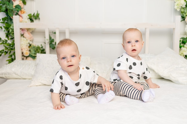 Dois bebês gêmeos de 8 meses de idade sentados na cama com as mesmas roupas