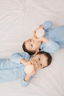 Dois bebês gêmeos de pijama estão deitados na cama bebendo leite de garrafas. vista de cima. conceito de casamento e amizade. conceito de comida para bebê. espaço para texto