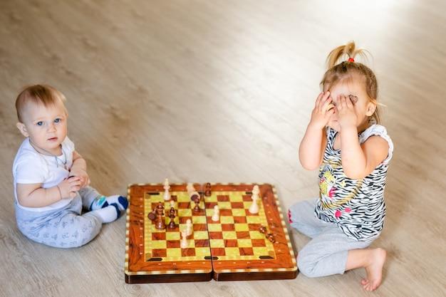 Dois bebês menino e menina jogando xadrez no chão de madeira branco em casa.