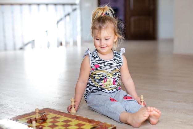Dois bebês menino e menina que jogam a xadrez no assoalho de madeira branco em casa.