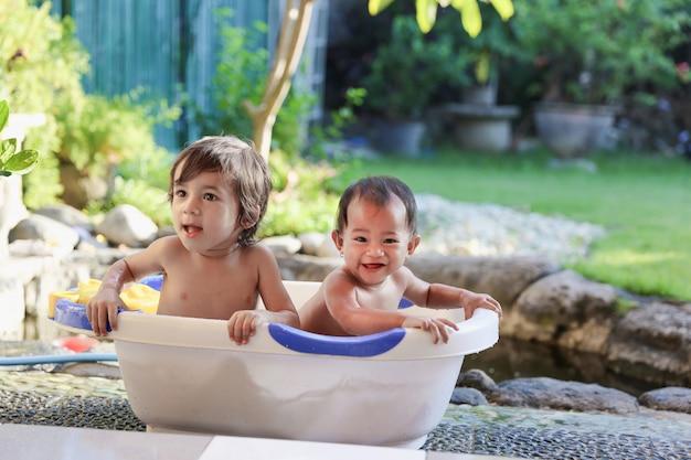 Dois bebês tomando banho juntos