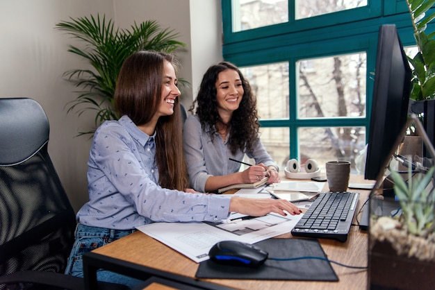 Dois belos designers ou arquitetos femininos resolvem conjuntamente tarefas de trabalho enquanto trabalham no escritório moderno perto da janela. pessoas criativas ou conceito de negócio de publicidade.