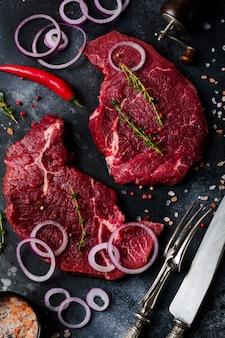 Dois bife de carne crua com especiarias, cebola e pimenta em ardósia escura ou fundo de concreto. vista do topo