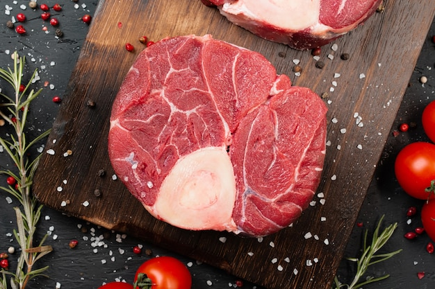 Dois bife de carne crua fresca em mármore em fundo escuro, tomate cereja e especiarias. fechar-se.