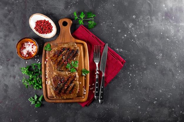 Dois bifes cozidos na grelha em uma tábua de madeira