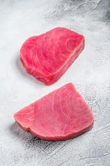 Dois bifes de atum crus na mesa rústica.