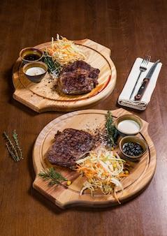 Dois bifes de carne com legumes e verdura na mesa de madeira em um restaurante de luxo