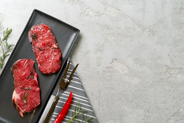 Dois bifes de carne crua fresca na placa de cerâmica preta