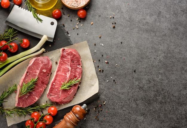 Dois bifes marmorizados e ingredientes do jantar vegetais de carne e condimentos em um fundo escuro com espaço de cópia