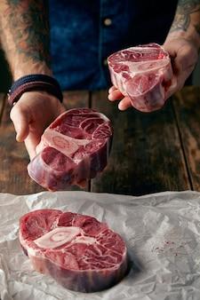 Dois bifes nas mãos tatuadas e outros em papel artesanal. ofereça-se para comprar carne diante da câmera.