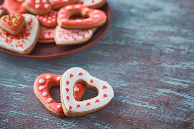 Dois biscoitos da forma do coração e muitos biscoitos decorados no fundo cinzento. conceito dia dos namorados