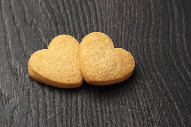 Dois biscoitos em forma de coração na mesa de madeira