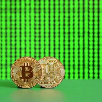 Dois bitcoins de ouro encontram-se na superfície verde no fundo da tela