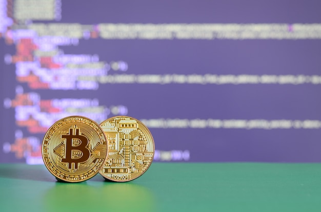 Dois bitcoins de ouro encontram-se na superfície verde