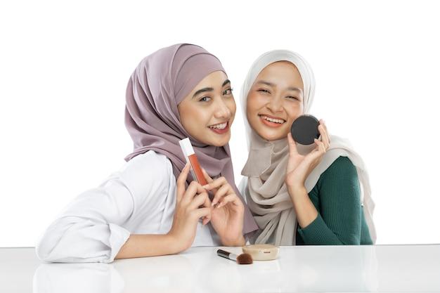 Dois blogueiros em hijab segurando maquiagem e cosméticos fazendo um vídeo de beleza