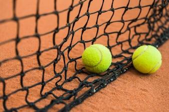 Dois bola de tênis perto da rede preta no chão