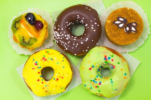Dois bolos castanhos e redondos. três donuts glaceados