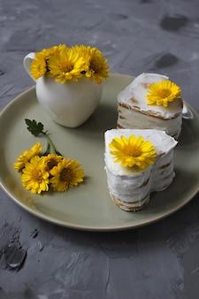 Dois bolos de mel em forma de coração com decoração de flores amarelas na placa cerâmica