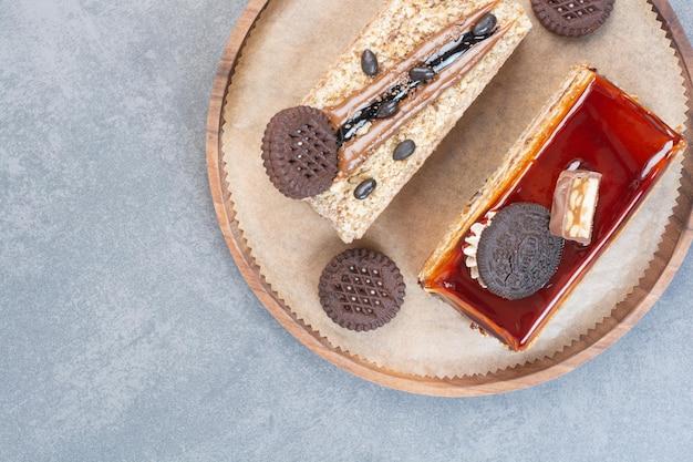 Dois bolos deliciosos e doces com biscoitos na tábua de madeira
