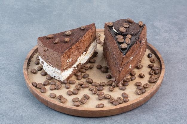 Dois bolos deliciosos e doces com grãos de café na placa de madeira