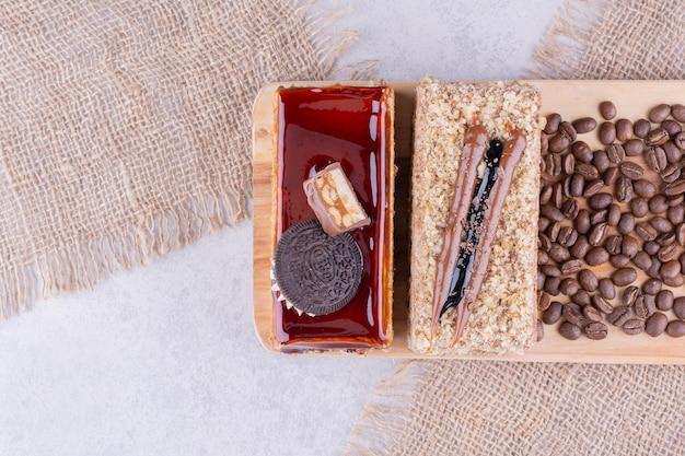 Dois bolos e grãos de café na placa de madeira. foto de alta qualidade