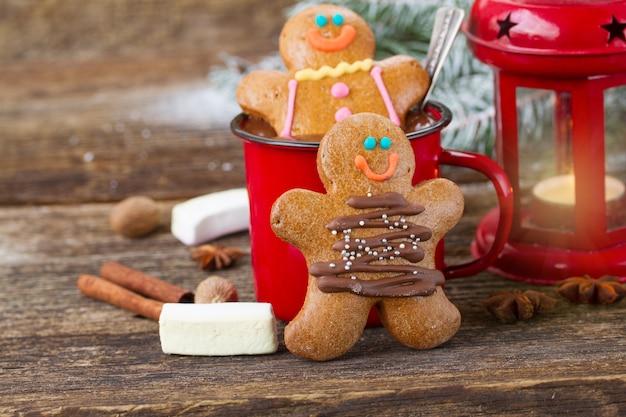 Dois bonecos de gengibre caseiros tradicionais na mesa de madeira com chocolate na caneca vermelha