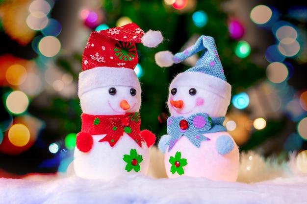 Dois bonecos de neve de brinquedo sob a árvore de natal no bokeh brilhante de fundo _
