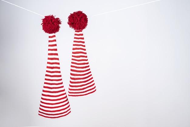 Dois bonés listrados de vermelho e branco com cauda longa e grandes pompons vermelhos pendurados em uma corda branca
