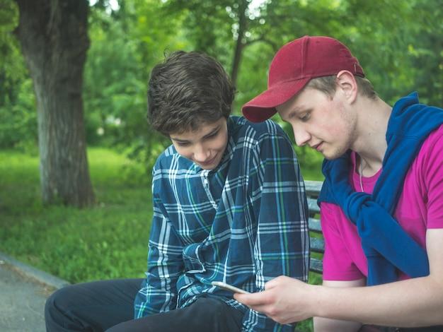 Dois, bonito, guys jovens, verificar, notícia alimenta, em, rede social, ao ar livre, ligado, um, verão, dia, parque