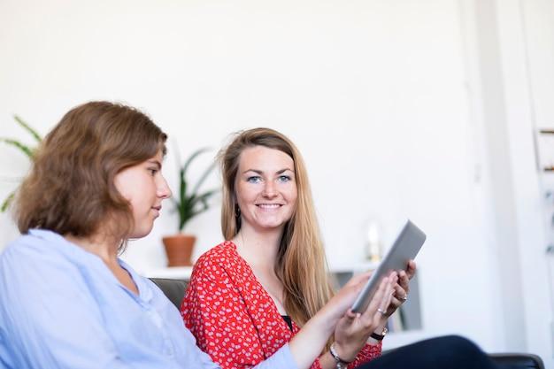 Dois, bonito, mulheres jovens, casa, sentar sofá, enquanto, usando, um, tabuleta, computador pc, e, sorrindo