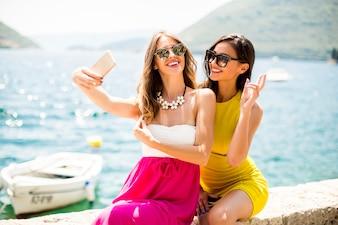 Dois, bonito, mulheres jovens, levando, selfie, com, telefone móvel, por, a, mar