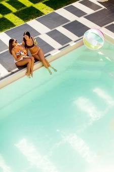 Dois, bonito, mulheres jovens, relaxante, por, a, piscina