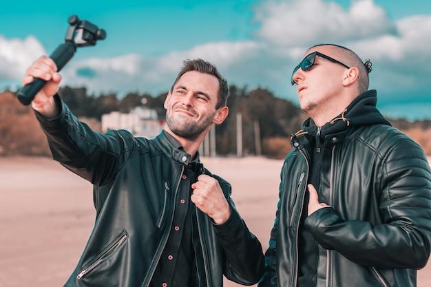 Dois bonitos amigos do sexo masculino fazendo selfie usando a câmera de ação com estabilizador de cardan na praia.