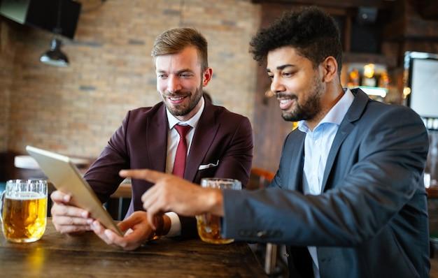 Dois bonitos homens de negócios se reúnem em um restaurante