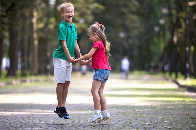 Dois bonitos jovens engraçados crianças sorridentes, menina e menino, irmão e irmã, pulando e se divertindo no parque ensolarado brilhante turva.