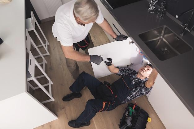 Dois bons encanadores na cozinha consertando a pia de água.