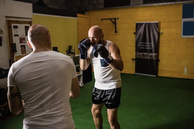 Dois boxeador praticando boxe no estúdio de fitness