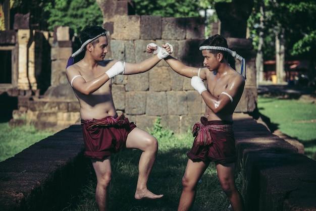 Dois boxeadores lutam com as artes marciais do muay thai.