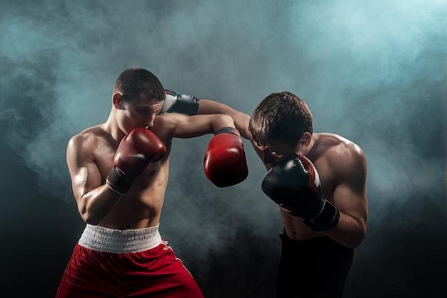 Dois boxeadores profissionais de boxe em fundo esfumaçado preto,