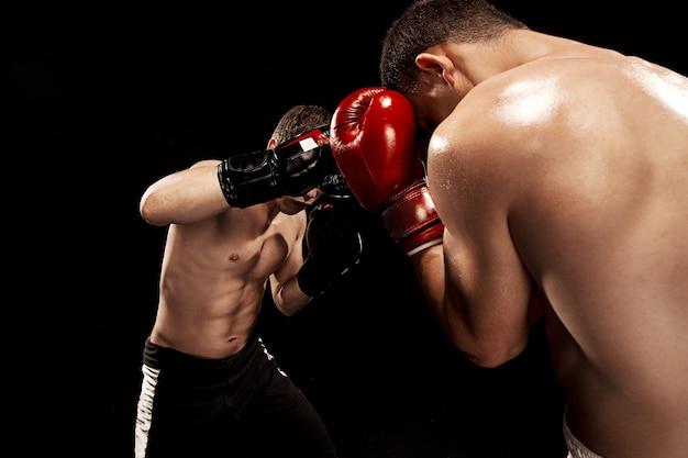 Dois boxeadores profissionais de boxe na parede preta