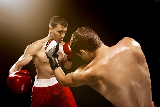 Dois boxeadores profissionais de boxe na parede preta,