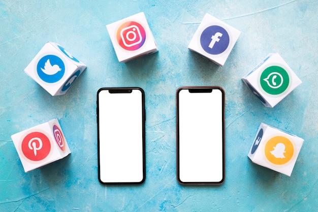 Dois brancos em branco celular rodeado com blocos de redes sociais na parede pintada